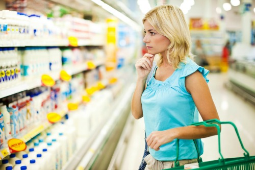 Young blonde woman shopping dairy food in food store.